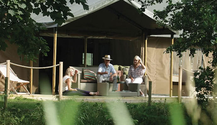 Family enjoing time on the deck of their luxury glamping tent